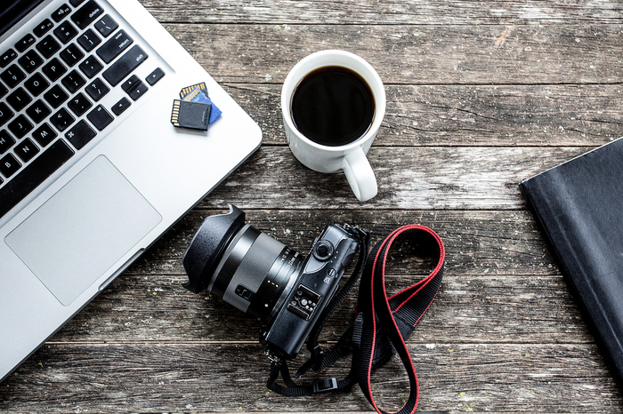 Laptop with digital camera and a coffee cup.